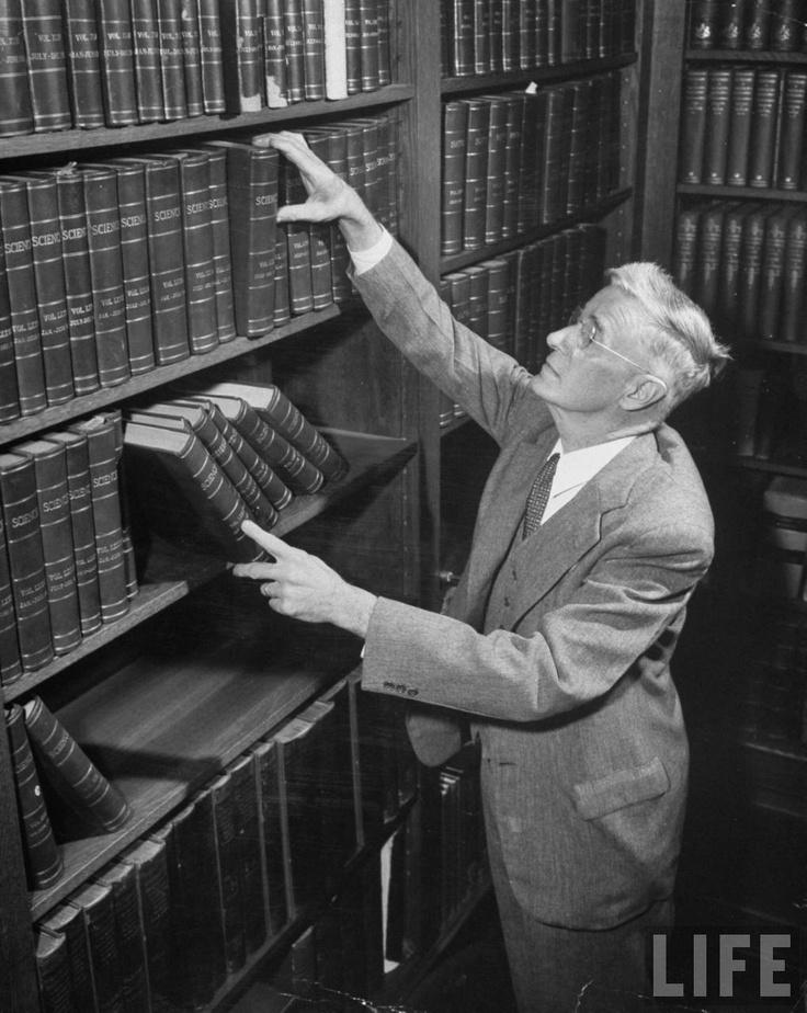 Dr. Vannevar Bush arranging books on bookshelf. (1947)