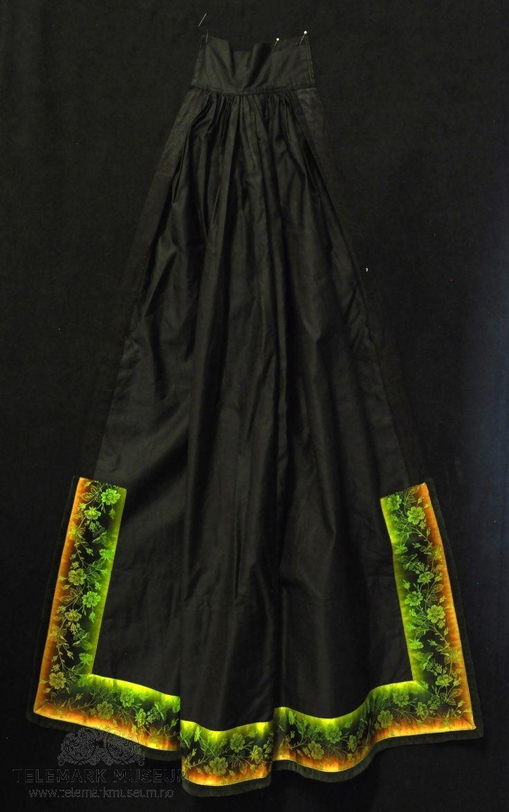 Fra protokollen: 1 kvindeforklæde Beltestakksforkle fra Bø - veldig smalt oppe (sein type - ant omkring 1890) og med kun ett bånd påsydd nederst på forkleet. Dette er til gjengjeld bredt og i flere farger. Stoffet i forkleet er silkesateng. Nederst (bak det påsydde båndet) på baksida er forkleet fôra med et mønstret bomullsstoff.