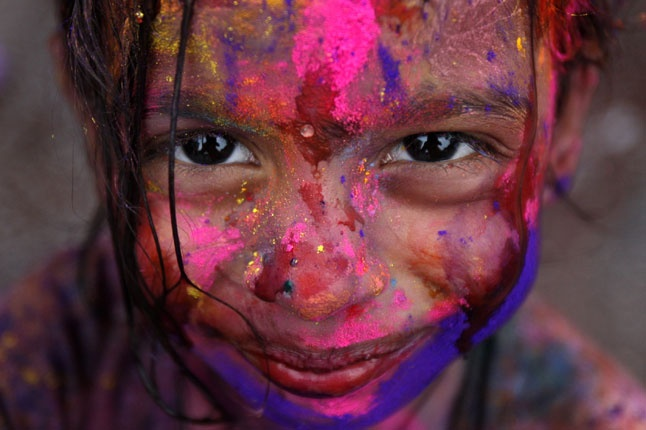 A girl smiles as her face is smeared with colored powder during the Holi festival in Kuala Lumpur (Condé Nast Traveller)