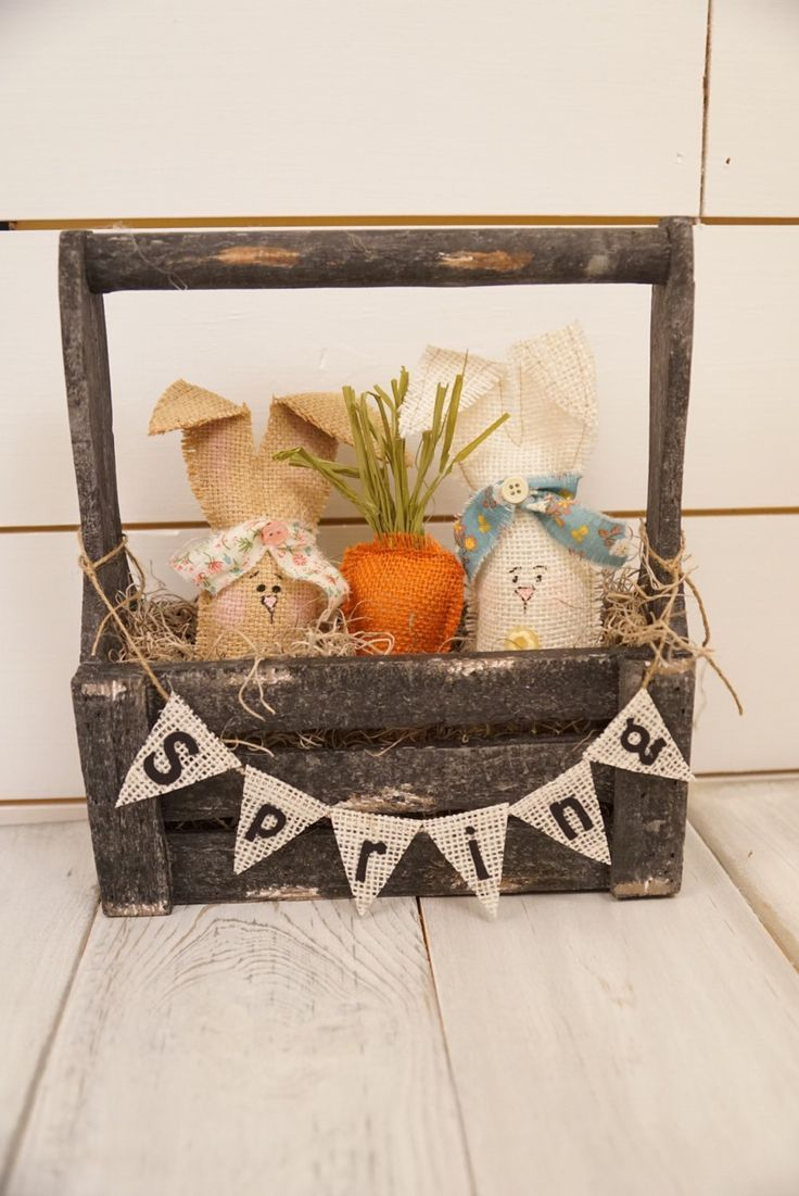 "Get ready for spring with this sweet bunny crate! Made with burlap bunnies, a carrot and a spring garland. This can sit anywhere on a table, window sill, or a shelf. The crate is approx 12"" X 8"" X 4"""