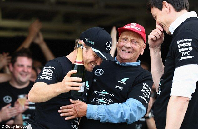 Rosberg celebrates along with Mercedes chiefs Niki Lauda (centre) and Toto Wolff