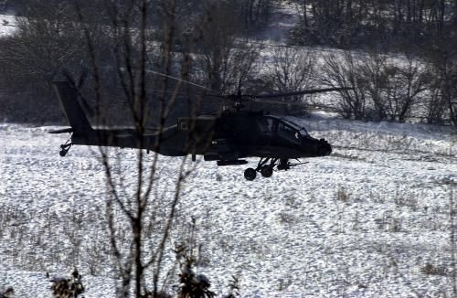 An AH-64A Apache helicopter hovers above the Heritage Drop Zone near Klina, Kosovo, in support of Operation JOINT GUARDIAN II