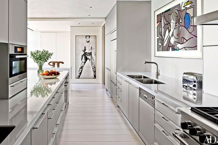 Art by Andy Warhol and Roy Lichtenstein hangs on the walls in the kitchen of a Chicago duplex apartment renovated by Marvin Herman & Assoc. The cabinetry and sink are by Bulthaup, and the faucet is by KWC.