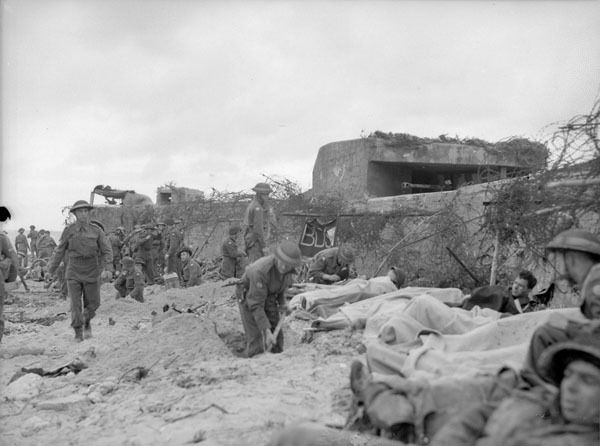 Wounded Canadian soldiers awaiting transfer to a Casualty Clearing Station of the Royal Canadian Army Medical Corps (R.C.A.M.C.) on D-Day, Courseulles-sur-Mer, France, 6 June 1944. Photographer: Frank L. Dubervill
