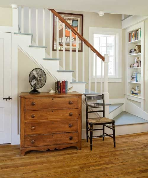 The former dead space over the kite-turn staircase in this farmhouse living room was carved out for shelving for books and collectibles. | Photo: Eric Roth | thisoldhouse.com