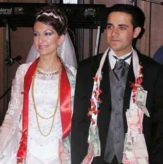 A Turkish bride wears a red sash with her wedding …