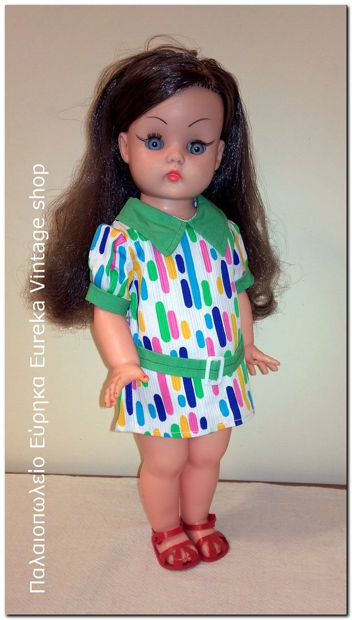 Ελληνική κούκλα Μπέλλα από την εταιρία του Αντωνίου Απέργη, από τα μέσα της δεκαετίας 1960's. Πολύ όμορφη με έντονες γραμμές eye liner και γκρι χρώμα ματιών, πλούσια μακριά καστανά μαλλιά. Είναι πολύ όμορφα ντυμένη.