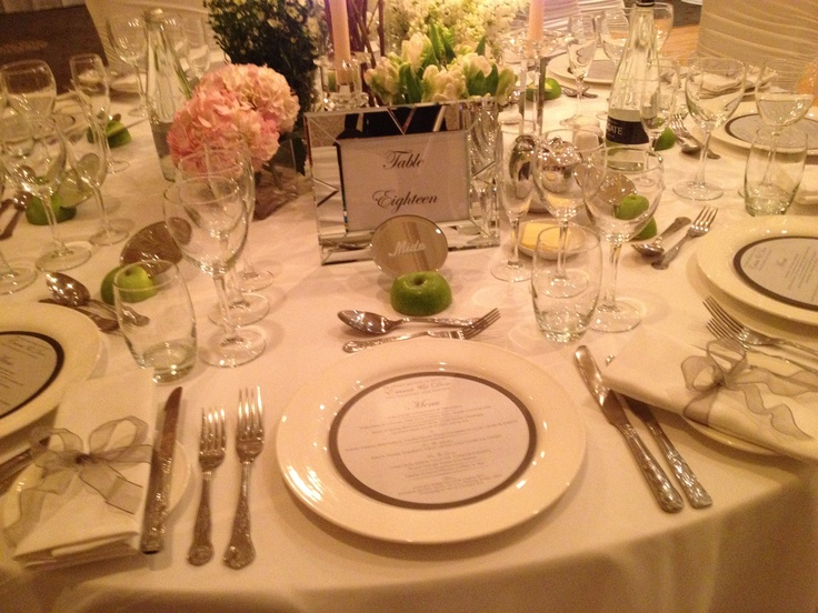 Table setting, menu printed on plate, and halved green apples holding the engraved guest name