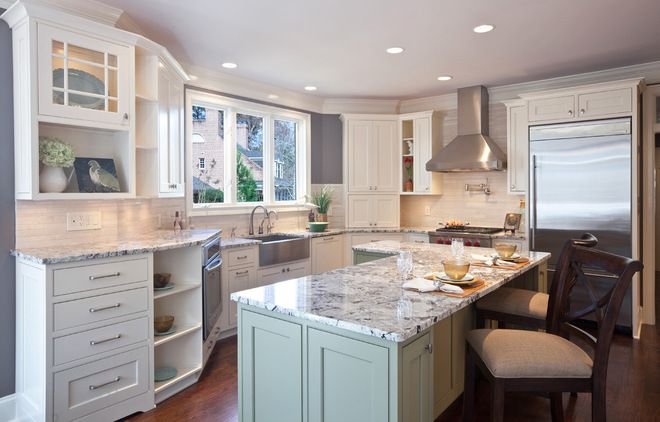 n this kitchen the island cabinets are painted duck-egg green, while the rest of the cabinets are left crisp white. The warm gray wall color...
