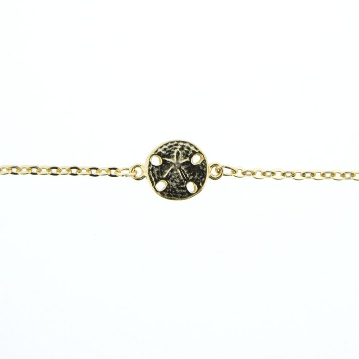 Gold Sand Dollar Anklet. Product Details: 9.5″ Anklet with 1″ Extender Tail. 5/8″ Sand Dollar. 22K American Gold Plated over brass chain & white metal charm. Lobster Claw Closure & Made in USA Tag. Made in America with Love. Comes on a R&R Card. Product Care: Store at room temperature, preferably in a jewelry box. Do not wear item in the ocean or shower. Put jewelry on after applying lotions, perfumes, or hairsprays. Clean with a polishing cloth- do not use jewelry cleaner, as it will…