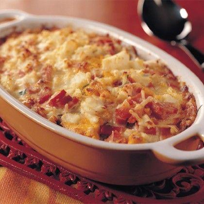 Snijd de blaadjes witlof in de lengte in brede repen. Snijd de aardappelen in plakjes. Hak de eieren fijn. Snijd de ham eerst in reepjes en daarna in stukjes. Verwarm de oven voor op 180°C. Verhit een klontje boter in een pan en roerbak de witlof kort. Laat afkoelen. Roer de kaas door de kookroom. Bestrooi een ingevette ovenschaal met wat paneermeel. Verdeel de aardappelschijfjes dakpansgewijs over de bodem van de schaal. Bestrooi met de fijngehakte selderij. Verdeel er het witlof over en…