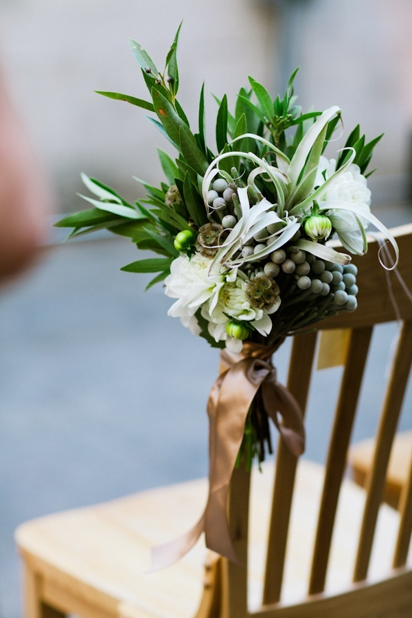 The first three rows of the ceremony aisle will be marked with clusters of seeded eucalyptus, bay laurel, olive branches, maidenhair fern, dripping jasmine vine, magnolia foliage, white scabiosa flowers, silver brunia, and ivory sweetpeas attached to the chairs with raffia.