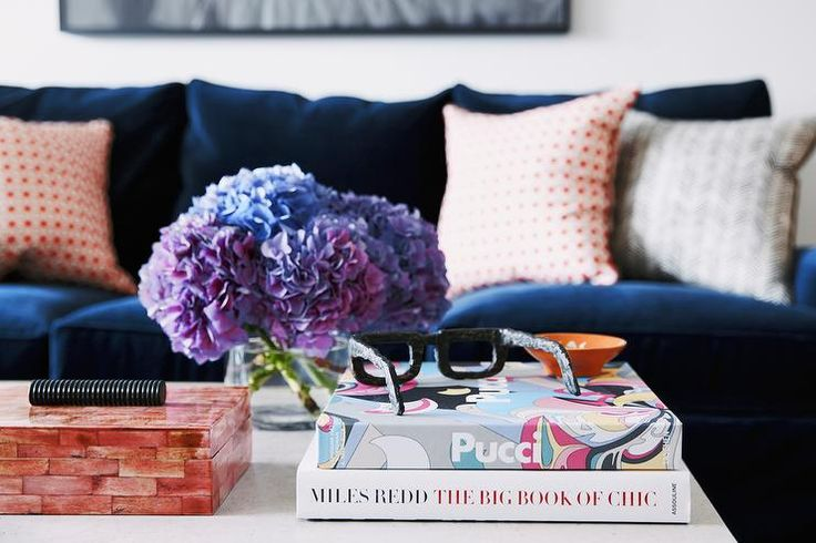 Contemporary living room features a navy velvet sofa adorned with orange garden lattice pillows and gray chevron pillow facing a white coffee table topped with an orange decorative box and  chic coffee table books.