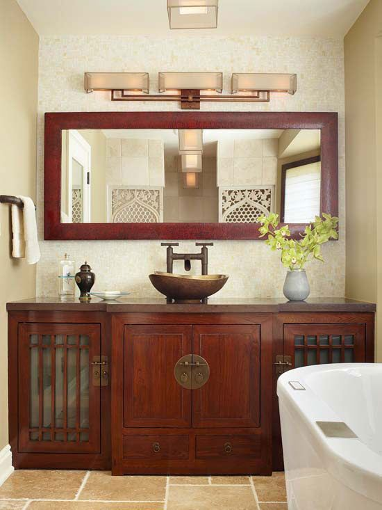 Asian Appeal A custom-designed wood vanity cabinet, featuring sleek lines, frosted glass, and brass hardware, blends effortlessly with the rest of this bathroom's Asian aesthetic. The center cabinets are adorned with round pulls reminiscent of a traditional Chinese wedding cabinet. The vanity's outer cabinets feature a geometric design accented by frosted-glass inserts.