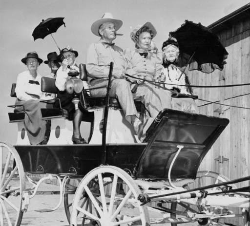 """View of people on a horse-drawn wagon, dressed period garb for a """"Pioneer picnic"""" in the San Fernando Valley, 1948. From left to right: Mrs. Lynn Wilcox, I. E. Ijams, Mrs. Alfred Prince, Mr. Fred Weddington, Frances Muir Pomeroy, Bessie Westerfield. San Fernando Valley Historical Society. San Fernando Valley History Digital Library."""