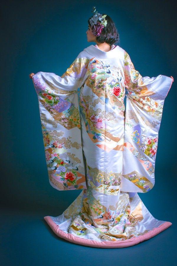 打掛『白地緞子色紙』、掛下『紫手刺繍花丸紋』光沢感のある緞子地に、柔らかなペールトーンの細かな柄が詰め込まれた色打掛。黄色い花や、藤色の花、小さく飛ぶ鶴など、優しい印象が閉じ込められた一枚です。