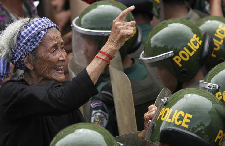 A woman gestures at police officers blocking a street during a protest in Phnom Penh, Cambodia, on June 17, 2013. (Credit: Samrang Pring/Reuters)