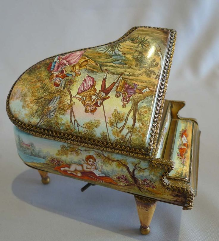 A fine quality antique musical box in the form of a miniature grand piano. Constructed of gilt bronze and hand painted Austrian enamel . All around the body of the piano it is painted with polychrome scenes of courting couples in rural idylls and with winged putti in orchards. The movement is key wound from below. Austria circa 1890.