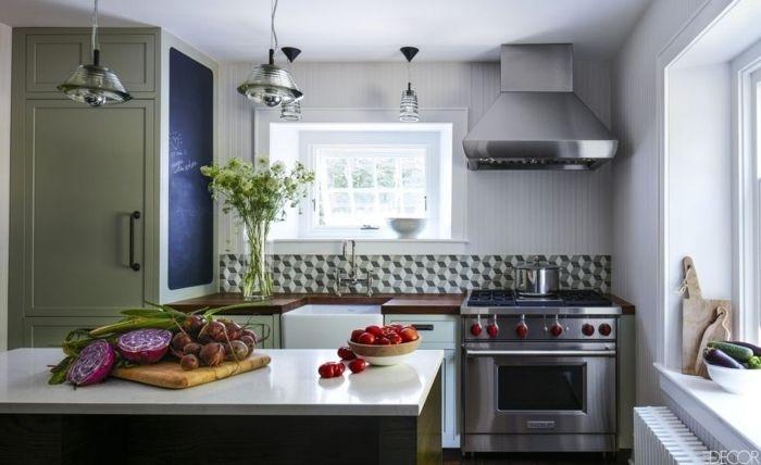 cocina pequeña con toque industrial, estufa y campana extractora metálicos, barra con verduras, larga pizarra