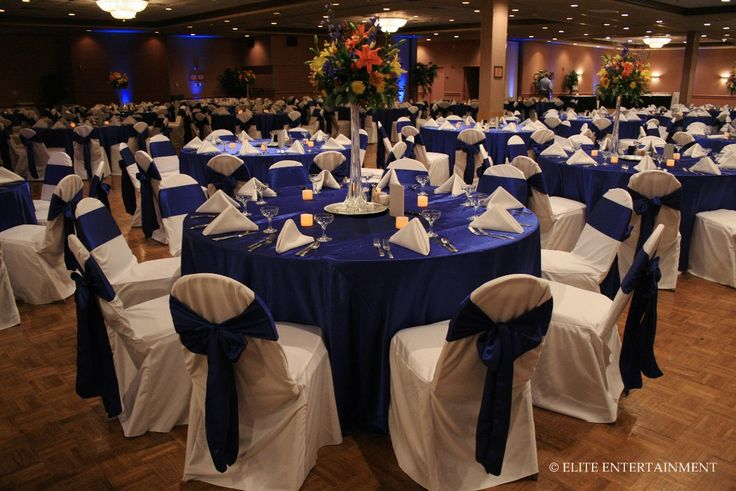 White chair covers(but spandex instead) with blue fold-over sash(instead of bow),  matching royal blue table linens, with silver chargers & white fold-over napkins(instead of this fold shown) for a more modern look :) Plus the blue uplights too!