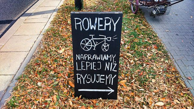 Rowery naprawiamy lepiej niż rysujemy. We repair bicycles better than we draw. Potykacz, sidewalk sign, a-board, a-frame, sandwich board