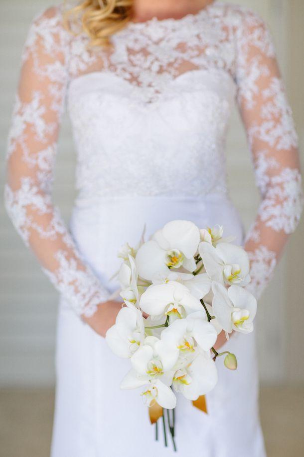 Lace sleeve wedding dress & white orchid bouquet | SouthBound Bride | http://www.southboundbride.com/chic-white-winter-wedding-at-rockhaven-by-kristi-agier-ashton-nic | Kristi Agier
