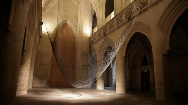 CATEN .  David Letellier. 2012  video  Created for the Saint Sauveur chapel in Caen, Caten is a levitating sculpture, determined by gravity and guiding the evolution of a sound composition.  300 fine wires suspended from two ropes, connected themselves at each end to a slowly rotating arm, form an evanescent surface which interacts with the architecture.