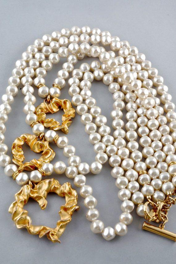 Caractéristiques : -100 % authentique GAVILANE PARIS. -3 brins / plusieurs niveaux de fausses perles avec 3 breloques coeur texturé. -Matériel de ton or. -Signé GAVILANE PARIS. -Fermeture à boucle bascule. -Excellent état vintage.  Mensurations : Petits coeurs: 1 5/8 po (4,12 cm) X 1 5/8 po (4,12 cm) Grand coeur: 2 3/8 po (6,03 cm) X 2 3/8 po (6,03 cm) Longueur: Taille unique  Ce collier sera expédié en colissimo avec numéro de suivi.  Sil vous plaît convo moi pour...