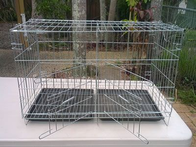 There is a galvanized small household pigeon cage that is divided into two parts, with two doors open but have nothing in it.