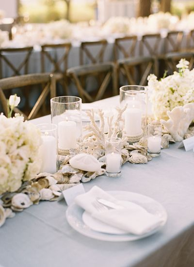Beach #wedding table decorations featuring white flowers, candles, coral and oysters.  So perfect for an oyster or clam bake reception!  #beachwedding #weddingdecor