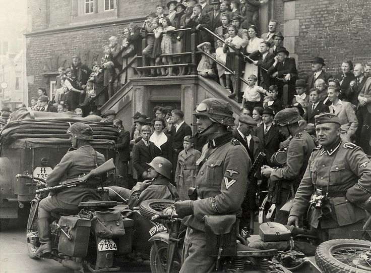 Waffen-SS soldiers with civilians. Notice the motorcyclist at left with a Haenel-Schmeisser MP-18 submachine gun and the SS registration plate on the car.