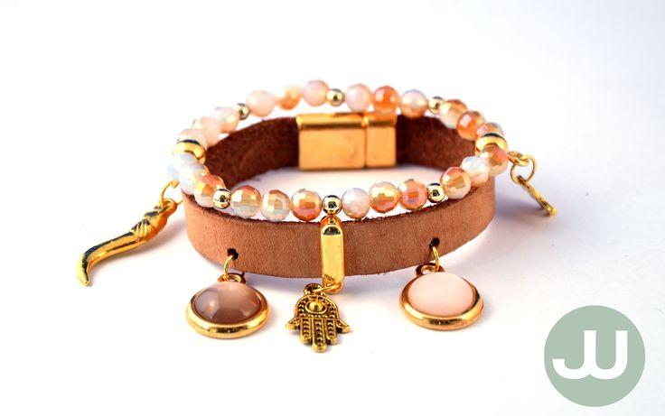 Armband met een bruine en een witte cabochon met gouden elementen op bruin leer, afgewerkt met een magneetsluiting. En een bijbehorende armband op elastiek met bruine kralen en gouden bedels.
