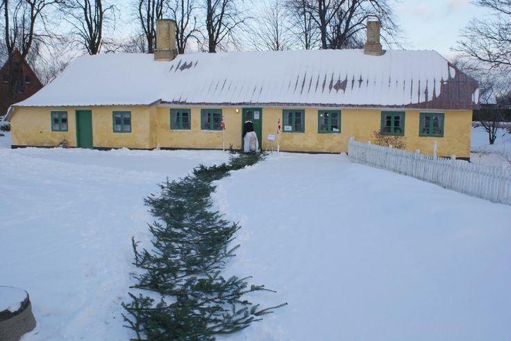 """Historie, Museum, Sognefogedgården, Frederikshavn, Danmark. Sneklædt gårdsplads med """"fruen"""" på vej ind i stuehuset."""