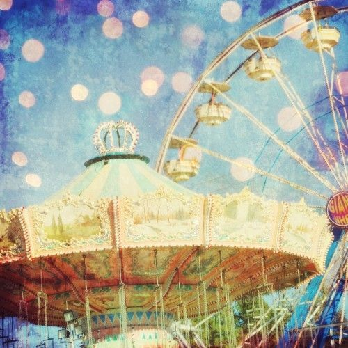 Photograph of a vintage carnival ride with the Ferris wheel in the background by Lupen Grainne