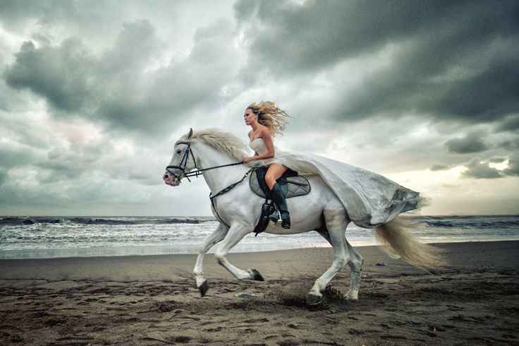 Horse riding bride!. I am so going to ride to my wedding!! Hitch up your wedding dress girls and prepare to canter cause you can now look elegant whilst horse riding on the beach!!. ❤️ This is an amazing plus down right beautiful idea for trash my dress too!. One of the best wedding photo ideas ever!