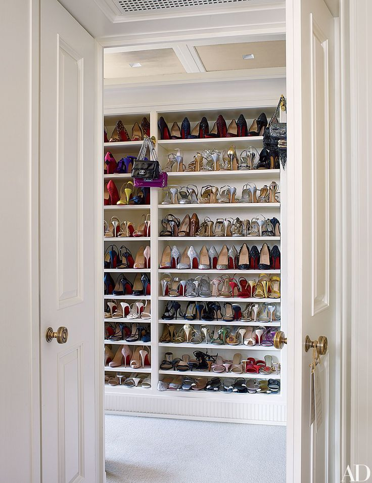 Shoes are displayed on custom-made shelving in a walk-in closet in a New York apartment designed by Michael S. Smith.