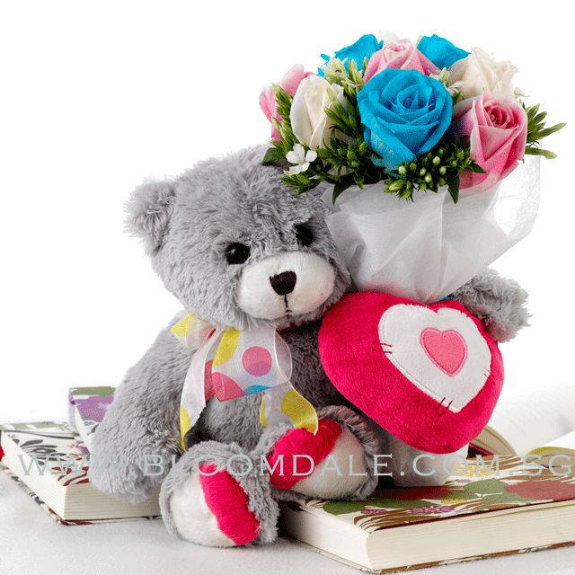 PS Test Item 01  Plush teddy Rainbow looks adorable with a cushioned heart attached to her, holding a beautiful bouquet of fresh Roses in Blue, Pink and Ivory. Approx Ht 17.5cm