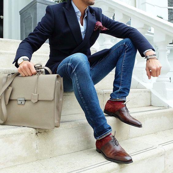 Acheter la tenue sur Lookastic: https://lookastic.fr/mode-homme/tenues/blazer-chemise-de-ville-jean-skinny/18983   — Chemise de ville bleue claire  — Pochette de costume á pois bordeaux  — Montre en cuir noir  — Serviette en cuir beige  — Jean skinny bleu  — Bracelet blanc  — Chaussettes rouge  — Chaussures richelieu en cuir brunes  — Blazer bleu marine