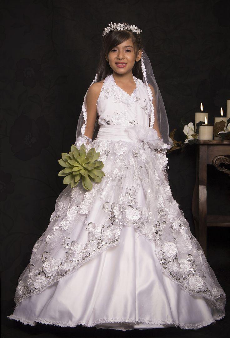 REF.14-46 Vestido de primera comunión entero con amarres en el cuello, su diseño es con bellas flores que cubren todo el vestido acompañados de lentejuelas plateadas, las cuales dan un toque más sutil y angelical.