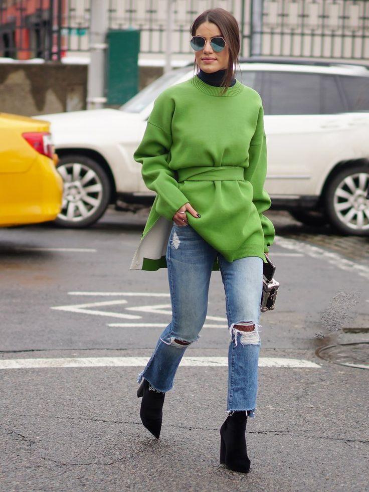 Street style de inverno de Camila Coelho na NYFW, com bota preta, calça jeans destroyed e casaco greenery com gola rolê preta e óculos