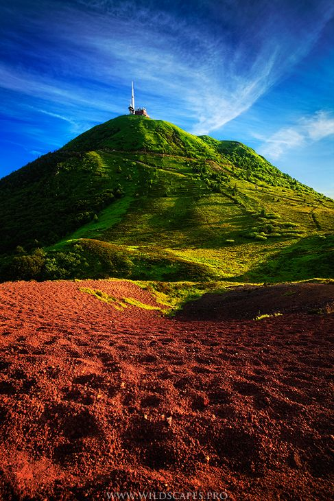 """Late afternoon view of """" le Puy de Dôme """" from its north face.  The foreground is composed of red volcanic rocks."""