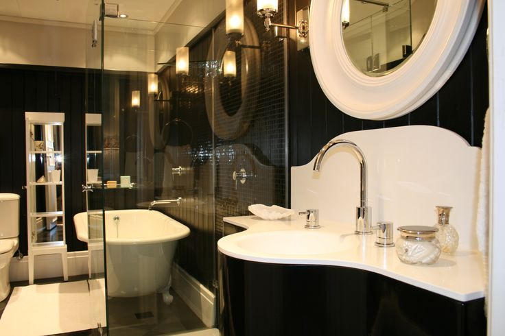 Black paneled walls and custom resin basin unit with a steel frame.