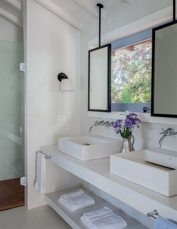 Piso e bancada (2,40 x 0,60 m e 12 cm de espessura) foram cobertos com tecnocimento branco no banheiro da suíte. Detalhe curioso, os espelhos pendentes fcam presos no teto, diante da janela basculante (2 x 0,60 m). Tudo para garantir farta luz natural e vista do jardim.
