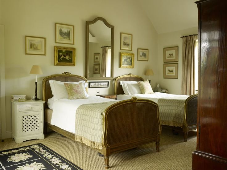 English country bedroom with mirror between twin beds, framed art