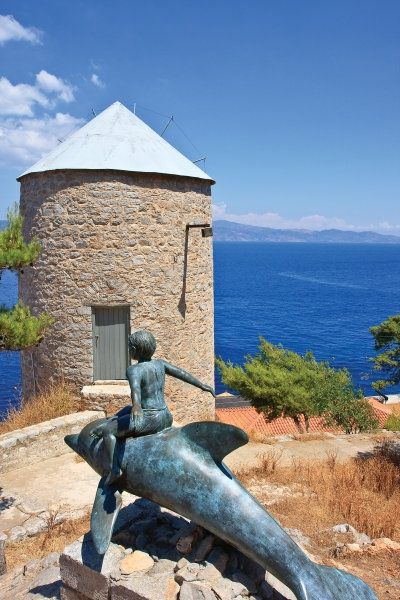 Boy on a Dolphin sculpture and windmill high over spilios cave, in memory of the film made on Hydra, Greece