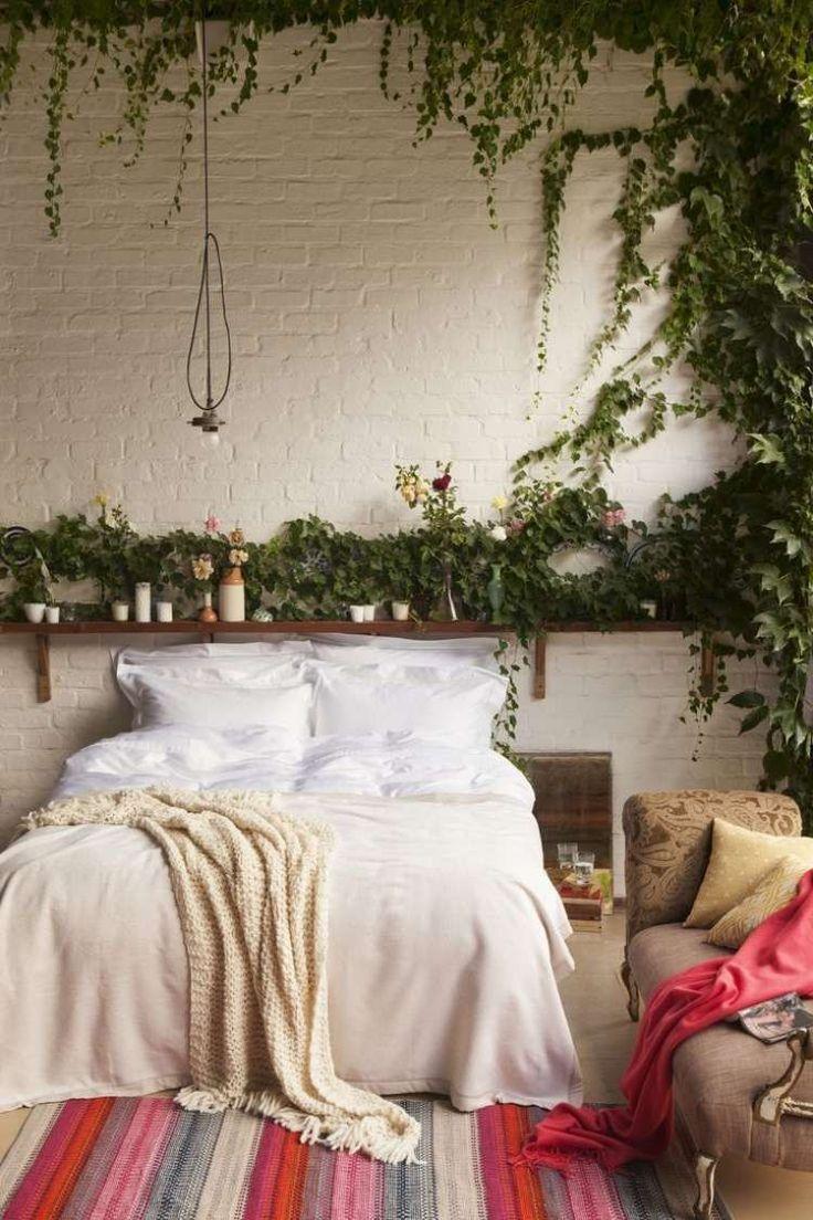chambre à coucher avec un mur de brique blanche, plantes grimpantes, literie en blanc et beige clair