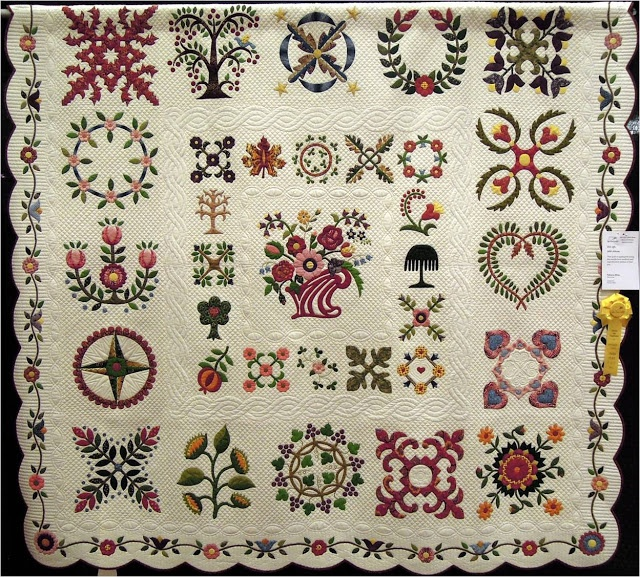 "1850 Album by Patricia Bliss, 2013 Arizona Quilters' Guild show, photo by Quilt Inspiration.  Third place winner for Best Applique in the Large Quilts category,  Patricia writes,  ""This quilt is appliqued using the needle-turn method and reproduction fabrics of that era.""  She created an inner border with smaller versions of Baltimore Album motifs."