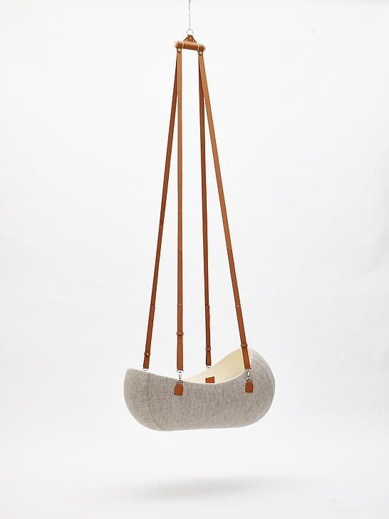 Inspired by a baby's experience in the womb, this modern cradle is suspended and reacts gently to every move or wiggle by a baby.
