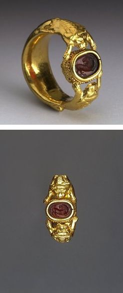 Etruscan. Gold Ring. 5th Century BC. This Gold finger-ring has two crouching lions on either side, the forepaws of which are outstretched and support a scarab in a gold band-setting. The engraved design depicts a lion with its head turned back. Gold work after A.D.