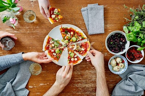three people sharing organic delicious pizza at dinner party friends eating hands taking pieces of pizza